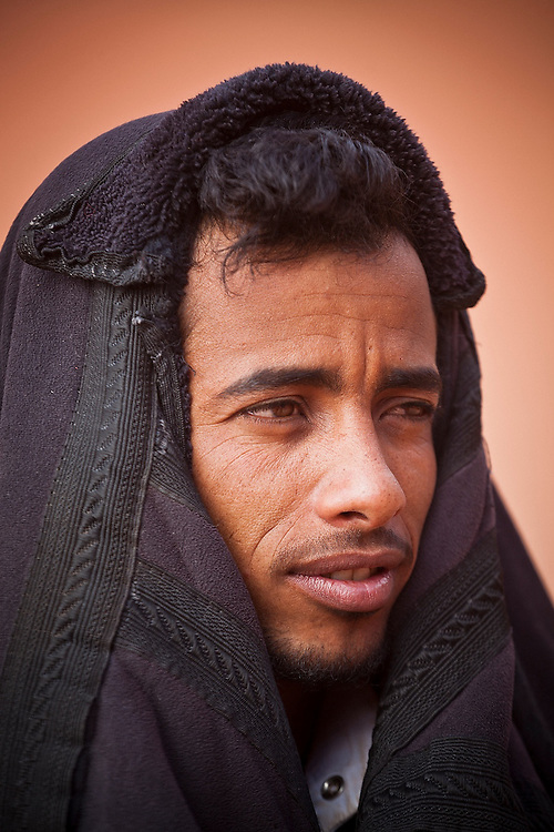 A Bedouin guide stays warm under his coat at the Bedouin Roads camp in Wadi Rum, Jordan.