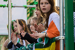 London, March 13th 2016. The annual St Patrick's Day Parade takes place in the Capital with various groups from the Irish community as well as contingents from other ethnicities taking part in a procession from Green Park to Trafalgar Square.  PICTURED: Children applaud from the back of a float. ©Paul Davey<br /> FOR LICENCING CONTACT: Paul Davey +44 (0) 7966 016 296 paul@pauldaveycreative.co.uk