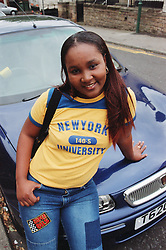 Portrait of teenage girl leaning against car smiling,