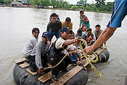 06 OCTOBER 2003 -- TAPACHULA, CHIAPAS, MEXICO: People from Guatemala ride on rafts across the Rio Suchiate towards the Mexican town of Hidalgo, near Tapachula. Tapachula is center of the smuggling industry between Mexico and Guatemala. Consumer goods are smuggled south to Guatemala (to avoid paying Guatemalan import duties) and people are smuggled north into Mexico. Most of the people coming north are hoping to eventually get to the United States. PHOTO BY JACK KURTZ