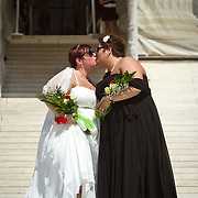 """Shannon Glatz, left, and Liberty Manos, of Akron Ohio, kiss to celebrate their marriage with twenty-four other couples as they traveled to Washington from Columbus Ohio, to get married en masse in front of the Supreme Court of the United States, on June 21, 2013.  Written along the bottom of Glatz's shoe is """"I Am Somebody"""".  John Boal photography"""