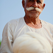 Man with traditional white clothes inside a Bishnoi family house