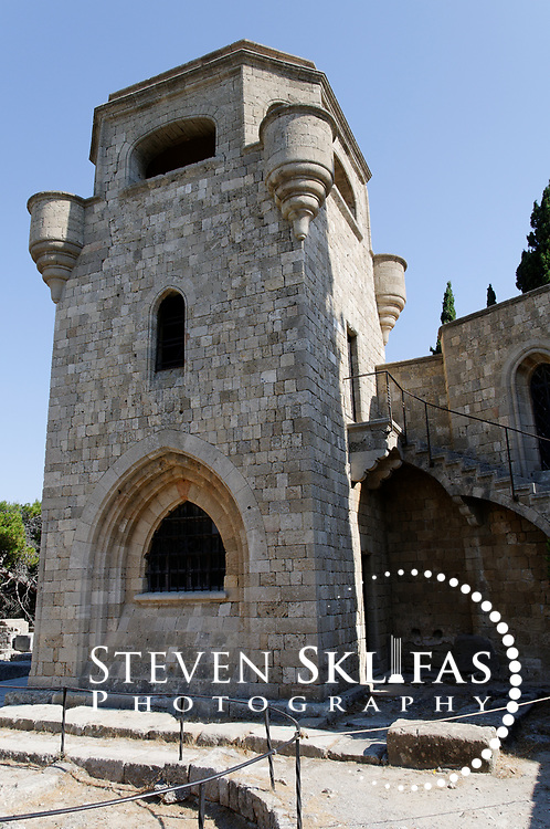 Rhodes. Greece. View of the 14th century golden walled Church of our Lady which was built by the Knights of St John and is the most impressive building at ancient Ialyssos. The structure includes chapels and a monastery, which were all faithfully restored by the Italians during their occupation of Rhodes in the early 20th century. In front of the church is a sunken 6th century baptismal font. Situated on the acropolis of Mt Filerimos on the verdant windswept west coast of Rhodes, Ialyssos is an outstanding fusion of ancient Doric, Byzantine and medieval archaeological remains and is one the finest sites of Rhodes Island. The island of Rhodes is the largest of the Dodecanese Island group and one of the most popular Greek Islands.