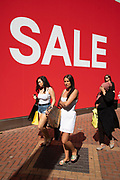People out shoppin walk past a large scale sale sign in white lettering on a red background outside H&M, a major high street clothing retail shop in Birmingham, United Kingdom. Its time for the summer sales, and most shops are advertising big reductions in prices. Bargains are avaiable and the shopping streets are busy.