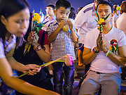 04 MARCH 2015 - BANGKOK, THAILAND: A boy drinks an iced tea while his parents pray at Wat Benchamabophit on Makha Bucha Day. Makha Bucha Day is an important Buddhist holy day and public holiday in Thailand, Cambodia, Laos, and Myanmar. Many people go to temples to perform merit-making activities on Makha Bucha Day. Wat Benchamabophit is one of the most popular Buddhist temples in Bangkok.     PHOTO BY JACK KURTZ