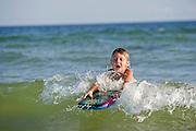 A boy boogie boards in the ocean in Fort Morgan, Alabama.