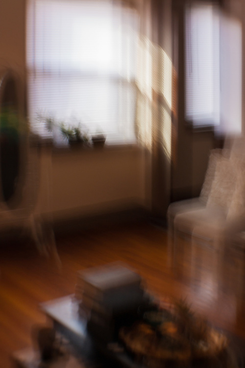 An apartment living room with light streaming in, rendered with intentional camera movement.