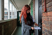 Volunteer Jessica Kleczka posts a leaflet for a local community support group called Mutual Aid through a letter box on a housing estate near the Caledonian Road in North London on 17th March 2020. Mutual Aid and other community support groups have grown significantly in the last few days as people volunteer to help their neighbours who are vulnerable or self isolating with things like shopping, getting prescriptions, and providing meals.  via Getty Images.