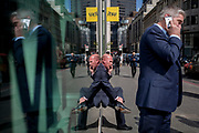 Symmetrical gentlemen talk on their phones reflected in plate glass in the City of London, the capital's financial district also known as the Square Mile, on 6th April 2017, in London, England.