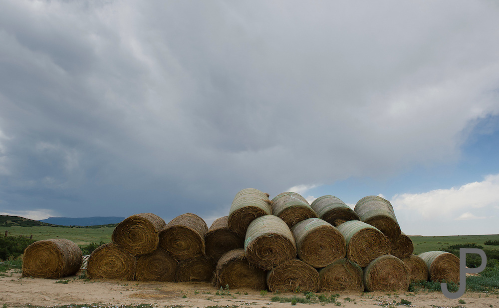 Colorado and New Mexico ranchers are busy in the spring cutting, baling and storing hay for the coming winter. This hay is stacked near a barn.  A major thunderstorms coming out of the Rockies brews in the background.