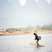 Young boy crossing river on raft, Guilin, Guangxi Province, China.