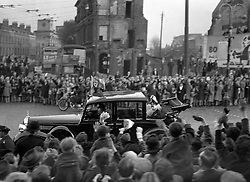 King George VI and Queen Elizabeth in an open car passing through the bond-damaged East End of London during their Stae drive in celebration of their Silver Wedding anniversary.