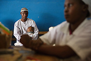 Diallo Mamadou Kalidou, 9 months, who suffers from anemia and malaria, sits on his father Diallo Amadou, 25, as they wait at the Libreville health center in Man, Cote d'Ivoire on Wednesday July 24, 2013.