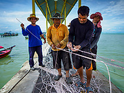 23 AUGUST 2018 - TELUK BAHANG, PENANG, MALAYSIA: Crewmen on a commercial fishing trawler in Teluk Bahang, on the island of Penang, sorts lines used to drag nets. Fishermen on Penang, an island off the west coast of mainland Malaysia, are being pressured by the island's resort development and reduce catches in the waters off Malaysia.     PHOTO BY JACK KURTZ