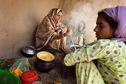 Mukhtar Mai, 33, cooks lunch at her house with family members, including, sister-in-law Shameem Mai, 32, Meerwala, Pakistan, April 27, 2005. Mai, went against the Pakistani tradition of committing suicide when she brought charges against the men who gang raped her nearly three years ago. With money from the ruling she opened two schools, one for girls, the other for boys. Mai cited that education is the only thing that will stop such acts from happening.