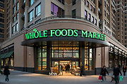 The Whole Foods entrance, on the northeast corner of The Bartlett in Arlington, Virginia, at twilight -- exterior design by Maurice Walters Architect