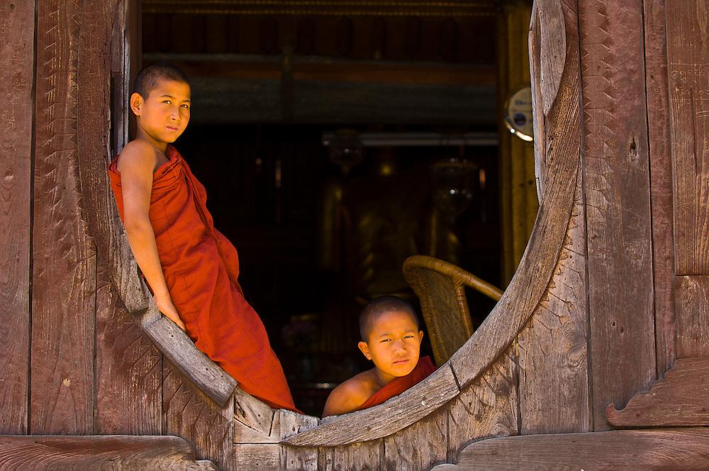Novice Buddhist monks looking out window in the Consecration Hall, Shwe Yaunghwe Kyaung Monastery, Nyaungshwe, Shan State, Myanmar, Burma