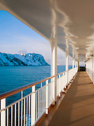 Windfarms sit atop snow covered hills, seen from a cruise boat at sea in Finnmark region, northern Norway