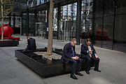 Businessmen check messages outside a financial institution in the Square Mile, the capitals financial district, on 3rd March 2017, in the City of London, England.