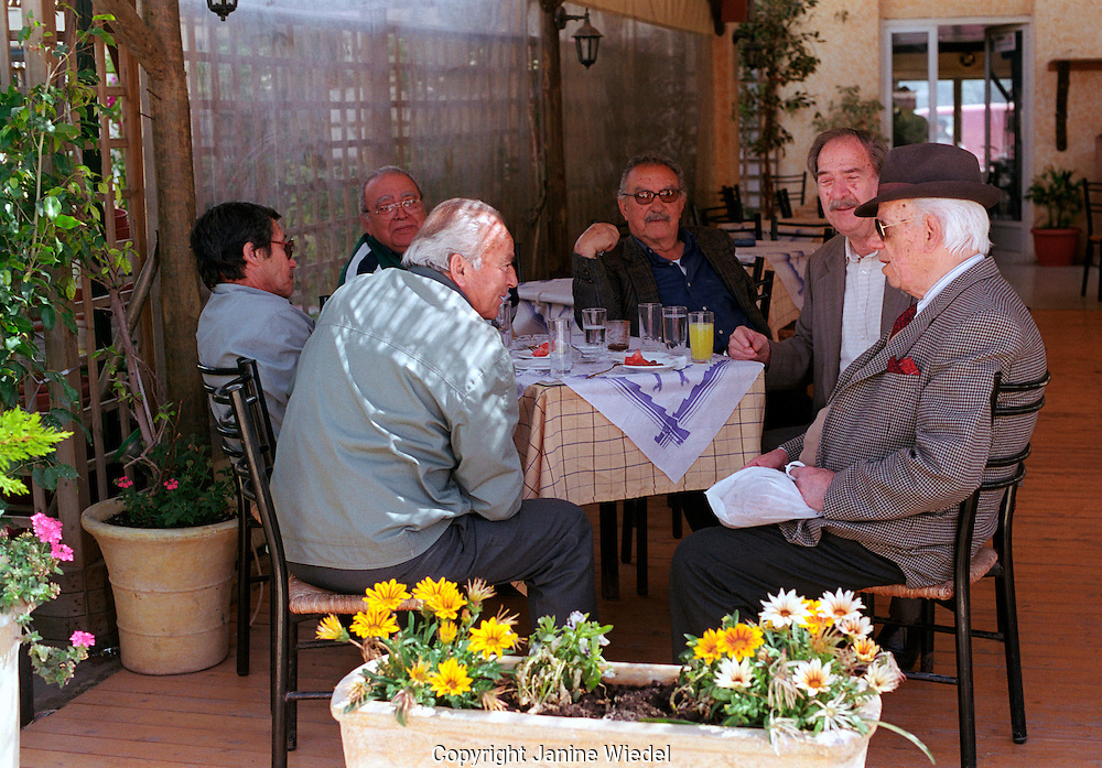 Group of older local men sitting in cafe bar chatting and drinking in Arastoli on Kefalonia Greek Island.