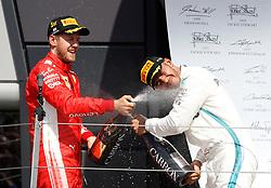 Winner, Ferrari's Sebastian Vettel and second placed, Mercedes' Lewis Hamilton spray champagne after the 2018 British Grand Prix at Silverstone Circuit, Towcester.