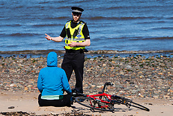 Portobello, Edinburgh. Scotland, UK. 11 April, 2020. Easter bank holiday weekend Saturday afternoon in very warm sunny weather the public are outdoors exercising and walking on Portobello beach. The popular beach and promenade was very quiet and people were mostly exercising proper social distancing. Pictured; Police patrolling the promenade stop to talk to a woman on beach. She was asked to move on.  Iain Masterton/Alamy Live News