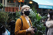 A young woman wearing a black face mask looks around Columbia Road Flower Market on 6th of December 2020 in Hackney, London, United Kingdom. The Sunday flower market in East London is on all year around for all kinds of plants and flowers but at Christmas time, many come to buy their Christmas trees and decorations for the festive season. The national lockdown 2 has just ended and London is under tier 2 restrictions, and while the pandemic is still raging, many wear face masks, even outside, because of the lack of social distancing.