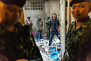 17 JANUARY 2014 - BANGKOK, THAILAND: Thai soldiers wait inside the doorway while anti-government protestors wait to get into an abandoned building they believe was used to plan to an IED attack on one of their marches. The attackers were not found but officials claim to have found a weapons cache in an abandoned building nearby. Friday was day 5 of the anti-government Shutdown Bangkok protests. The protest, led by the People's Democratic Reform Committee, is calling for the suspension of elections pending political reform in Thailand. There was violence at several sites in Bangkok Friday, including running battles between government opponents and supporters at one site and an IED attack by unknown assailants on anti-government protestors at another site.    PHOTO BY JACK KURTZ
