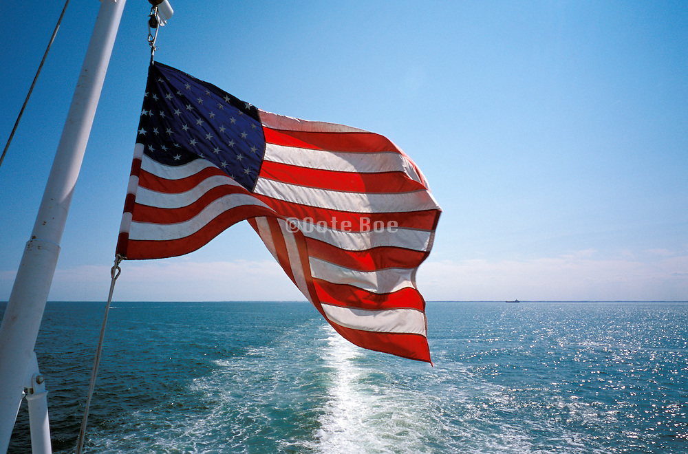 American flag blowing in the wind viewed from a boat