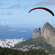 A para glider flying above the hillside of Pedro Bonita high in the hills of Rio de Janeiro. Pilots of hang gliders and para gliders take tourists for tandem flights with breathtaking views of the city before landing on Sao Conrado beach. Rio de Janeiro,  Brazil. 9th September 2010. Photo Tim Clayton
