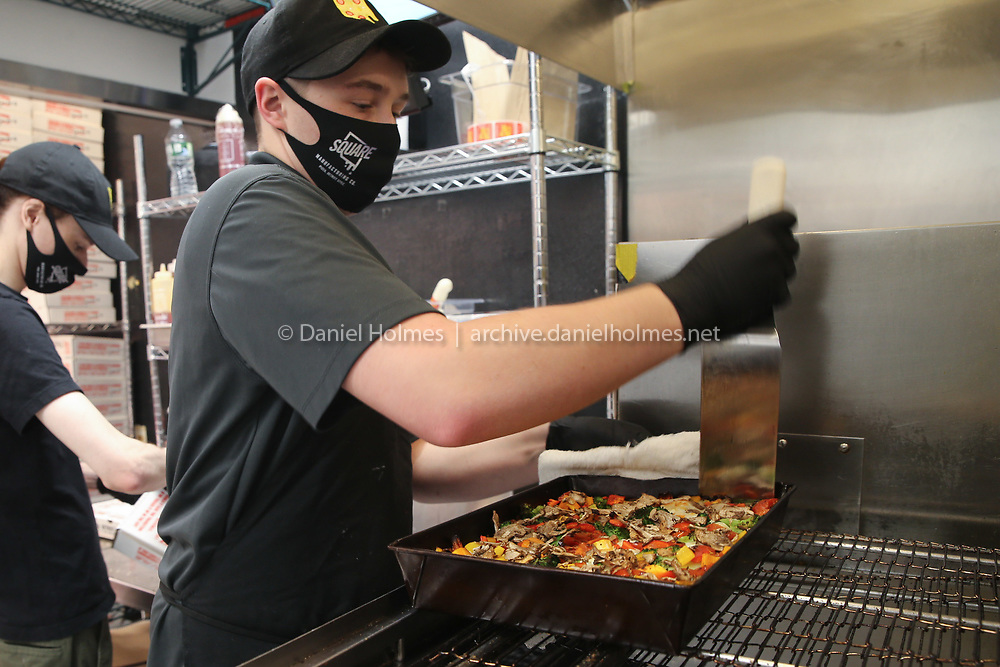 Employee David Craig takes a vegetable pizza from the oven at Square Mfg Co. in Natick on Jan. 05, 2021.