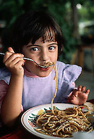 November 1989, Ischia, Italy --- A young girl eats bucatini in Ishchia, Italy. --- Image by © Owen Franken/CORBIS