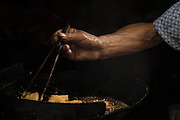 A street vendor prepares food in a wok, Xitang, Zhejiang, China