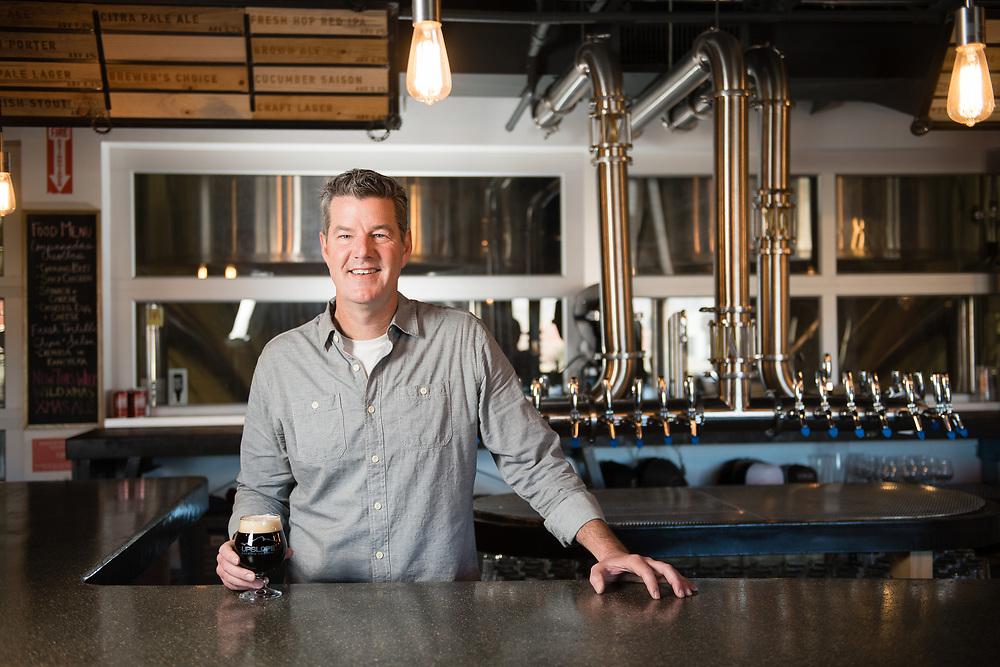 Portrait of Upslope beer owner behind the bar in Boulder, Colorado.
