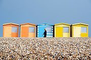 © Licensed to London News Pictures. 14/04/2015. Seaford, UK. A woman walks past colourful beach huts. People in the early morning sea mist and sunshine in Seaford today 14th April 2015. Today is expected to be a very warm day across Britain. .. Photo credit : Stephen Simpson/LNP