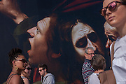 Visitors walk beneath the faces from The Taking of Christ (c1602) the painting of the arrest of Jesus, by Italian Baroque master Caravaggio and exhibited at the National Gallery, London.