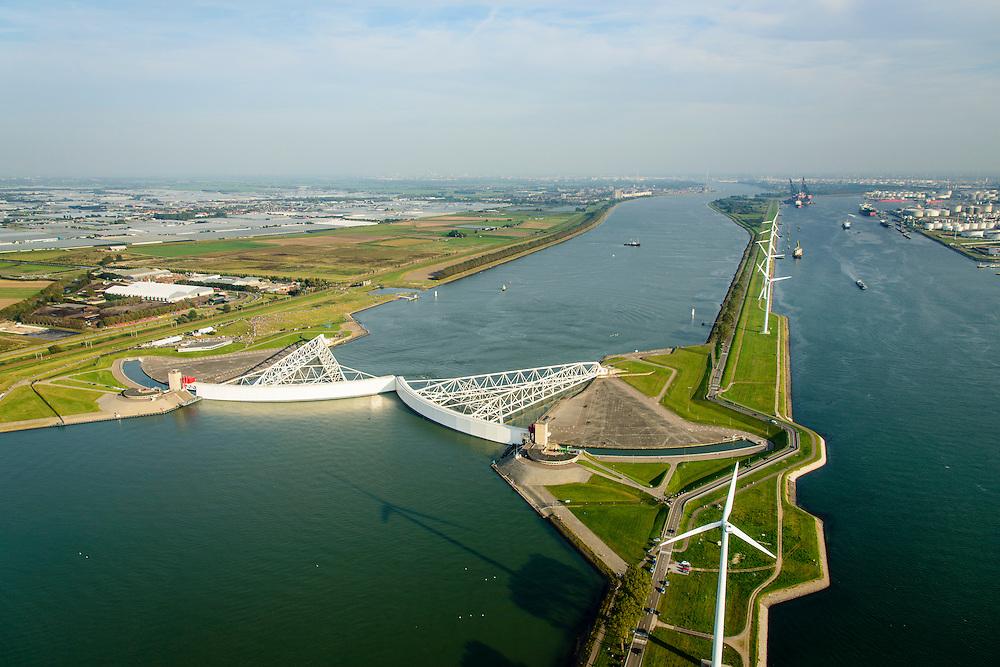 Nederland, Zuid-Holland, Nieuwe Waterweg, 28-09-2014; Functioneringssluiting Maeslantkering. De waterkering in de Nieuwe Waterweg wordt een maal per jaar, voordat het stormseizoen begint, getest. Tijdens het sluiten van de kering ligt alle scheepvaartverkeer naar de Rotterdamse haven stil. Aan de horizon Rotterdam, rechts Callandkanaal en de havens van Europoort. De Maeslantkering sluit normaal gesproken alleen bij dreigende stromvloed en bij een waterstand van 3 meter of meer boven NAP. De kering, onderdeel van de Deltawerken, vormt samen met de Hartelkering de Europoortkering en beschermt Rotterdam en achterland bij extreme waterstanden. <br /> Hoek van Holland - Port of Rotterdam. Aerial view of the new storm surge barrier (Maeslantkering) in the Nieuwe waterweg during the so-called functioning closure, taking place one a year before the storm season begins. The waterway, leading to the Port of Rotterdam (at the horizon), is closed during the test.<br /> luchtfoto (toeslag op standard tarieven);<br /> aerial photo (additional fee required);<br /> copyright foto/photo Siebe Swart