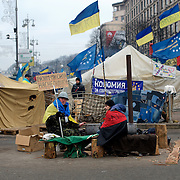 December 18, 2013 - Kiev, Ukraine: Pro-EU demonstrators, one holding a sign saying 'together we are powerful, we won't be overcome' sit in Independence Square.<br /> On the night of 21 November 2013, a wave of demonstrations and civil unrest began in Ukraine, when spontaneous protests erupted in the capital of Kiev as a response to the government's suspension of the preparations for signing an association and free trade agreement with the European Union. Anti-government protesters occupied Independence Square, also known as Maidan, demanding the resignation of President Viktor Yanukovych and accusing him of refusing the planned trade and political pact with the EU in favor of closer ties with Russia.<br /> After a days of demonstrations, an increasing number of people joined the protests. As a responses to a police crackdown on November 30, half a million people took the square. The protests are ongoing despite a heavy police presence in the city, regular sub-zero temperatures, and snow. (Paulo Nunes dos Santos/Polaris)