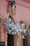 Silver branches and clusters of glass balls decorate a baroque stone doorway for Christmas in Oaxaca, Mexico.