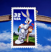 Noel Blanc, son of famous voice master, Mel Blanc whose voice for numerous cartoon characters including Bugs Bunny stands atop a Warner Brothers sign of a U.S. Post Office stamp of Bugs Bunny, Noel now does the voice of Bugs.