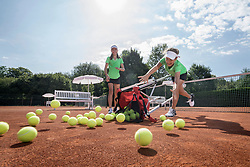 Two girls tipping a basket full of tennis balls, Bavaria, Germany