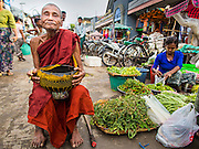08 NOVEMBER 2014 - SITTWE, RAKHINE, MYANMAR:  A Buddhist monk solicits alms at the entrance to the market in Sittwe. Sittwe is a small town in the Myanmar state of Rakhine, on the Bay of Bengal.  PHOTO BY JACK KURTZ