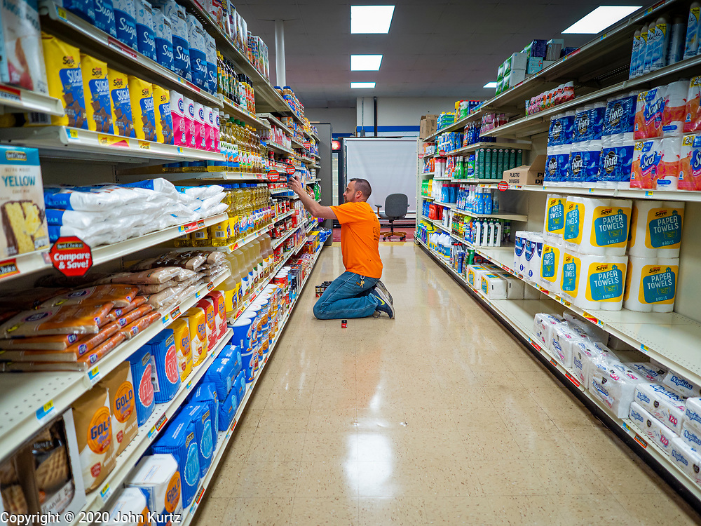 "30 JUNE 2020 - JEWELL, IOWA: GARREN ZANKER stocks the shelves in Jewell Market, the soon to reopoen grocery store in Jewell, IA. The only grocery store in Jewell, a small community in central Iowa, closed in 2019. After the store closed, Jewell became a ""food desert."" The grocery store had served four communities within a 20 mile radius of Jewell. Some of the town's residents created a cooperative to reopen the store. They sold shares to form a co-op, and they held fundraisers through the spring. Organizers raised about $225,000 goal and bought the store. They hope to reopen in the next week. The USDA defines rural food deserts as having at least 500 people in a census tract living 10 miles from a large grocery store or supermarket. There is a convenience store in Butterfield, but it sells mostly heavily processed, unhealthy snack foods that are high in fat, sugar, and salt.       PHOTO BY JACK KURTZ"