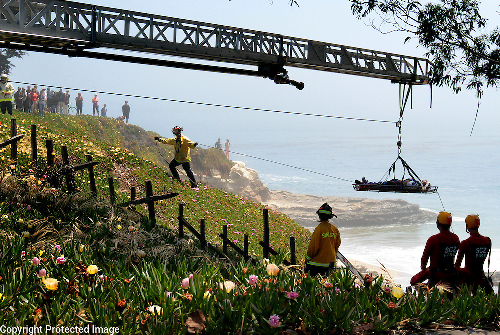 Santa Cruz firefighters hoist an injured man up to West Cliff Drive after he was reported lying motionless on the rocks 18-20 feet below the roadway at Fair Avenue in Santa Cruz, California on Sunday May 12, 2013. The man was breathing but unconscious and was airlifted to Stanford Hospital. <br /> Photo by Shmuel Thaler <br /> shmuel_thaler@yahoo.com www.shmuelthaler.com