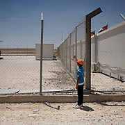 August 09, 2013 - Zarqa, Jordan: A syrian child looks through the fence at the visitors area in Mrigb Al-Fuhud refugee camp, also known as Emirates-Jordanian camp, 20 kilometres east of the Jordanian city of Zarqa.<br /> The 10 million USD camp, which has 750 caravans, a hospital, and a school and can take up to four thousand people, first opened in April 2013 and was paid for by the United Arab Emirates. Work is underway to house a total of 20 thousand by the end of the year.<br /> In contrast with the two other camps in the area, Mrigb Al-Fuhud as been classified by many as a 'five star' camp due to impressive housing facilities provided to the refugees. (Paulo Nunes dos Santos/Al Jazeera)