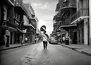 An african-american musician walks down a New Orleans street with his giant sousaphone