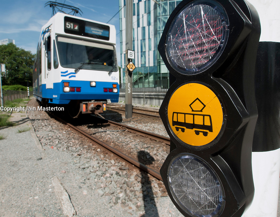 Tram at pedestrian crossing in modern business district at Amsterdam Zuid in The Netherlands