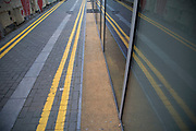 Double yellow lines painted onto a narrow road and reflected in a neaby window in London, England, United Kingdom.