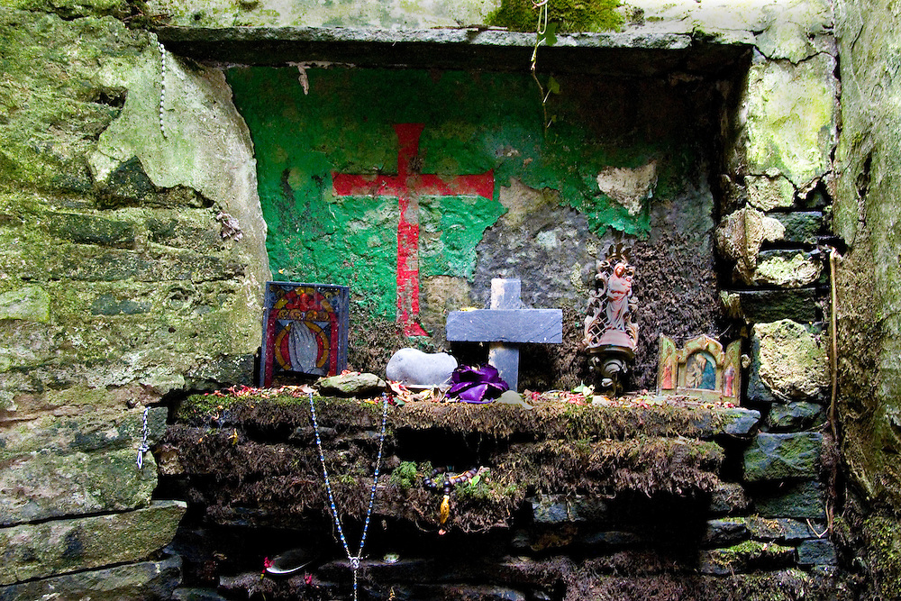 """On the Liscannor -  Doolin road, near the Cliffs of Moher, this ostensibly holy well is full of wonderful, decaying votive offerings. St. Brigid never actually existed in Christian times - in mythology she was the """"exalted one"""" - daughter of the Dagda and therefore one of the Tuatha De Danann.....The """"cave"""" at St. Brigit's Well is full of strange objects. Decaying statues, rotting dolls, faded masscards, abandoned prosthetic limbs, rosary beads, toys, polaroid photographs. All left as mementos, blessings, prayers for the dead, the ill and the future."""