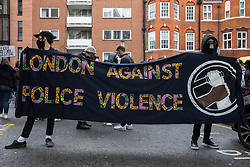 London, UK. 15th May, 2021. Activists stand behind a London Against Police Violence banner as hundreds of people attend a Free Palestine SOS Colombia solidarity rally outside the Colombian embassy. Speakers at the event highlighted human rights abuses such as forced displacement being directed against Palestinians in Israel and the Occupied Territories and the killing, repression, detention and torture of peaceful demonstrators and human rights defenders in Colombia.